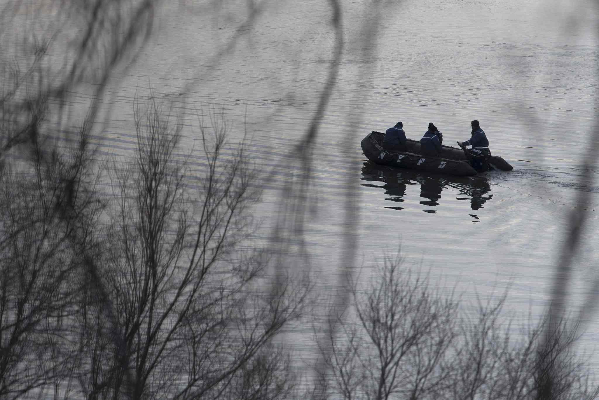 Emergency personnel patrol the waters near the scene the train derailment.