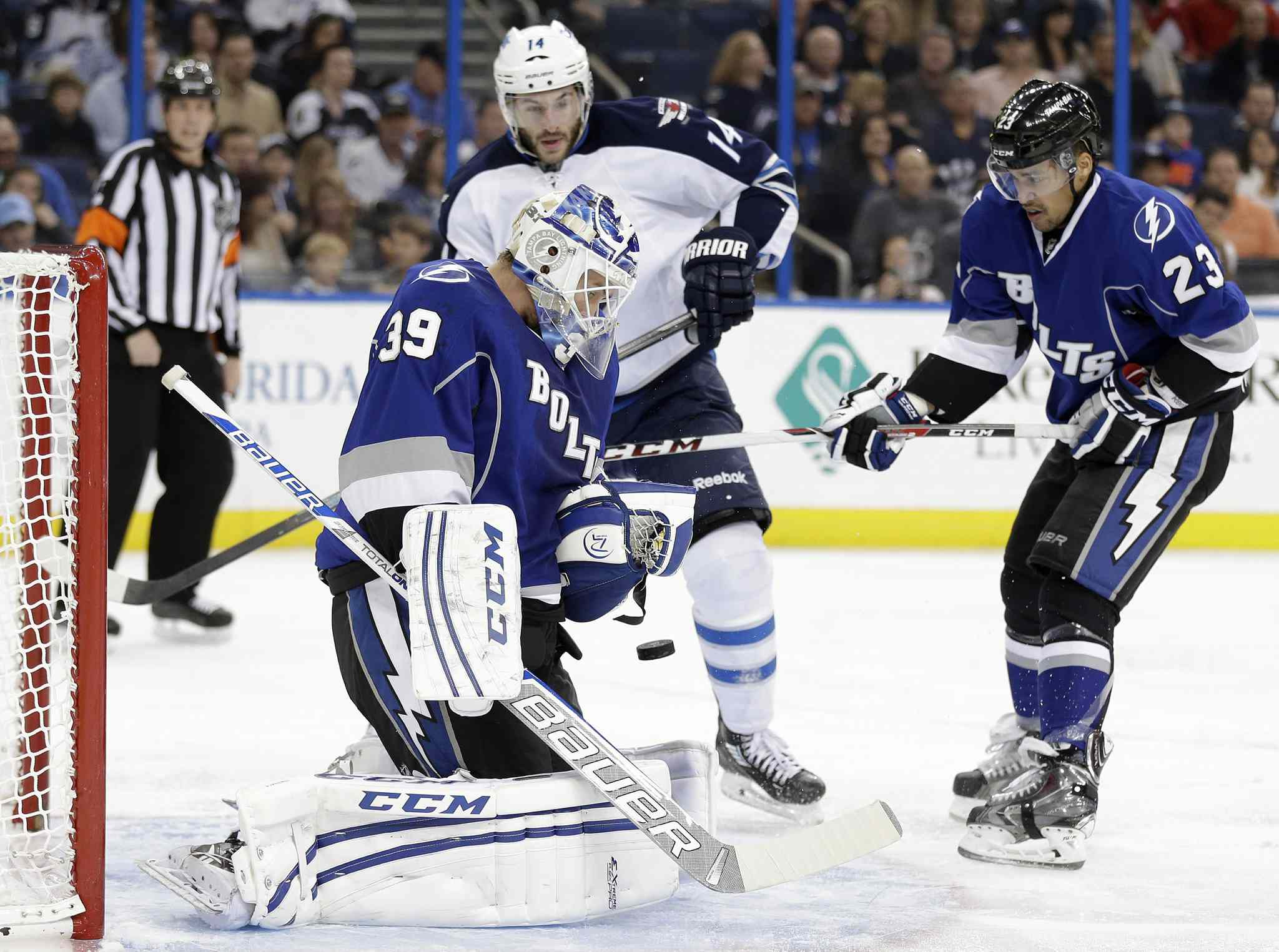 Tampa Bay Lightning goalie Anders Lindback (front)makes a save on a shot by Winnipeg Jets winger Anthony Peluso (centre) as Lightning's J.T. Brown defends during the third period.