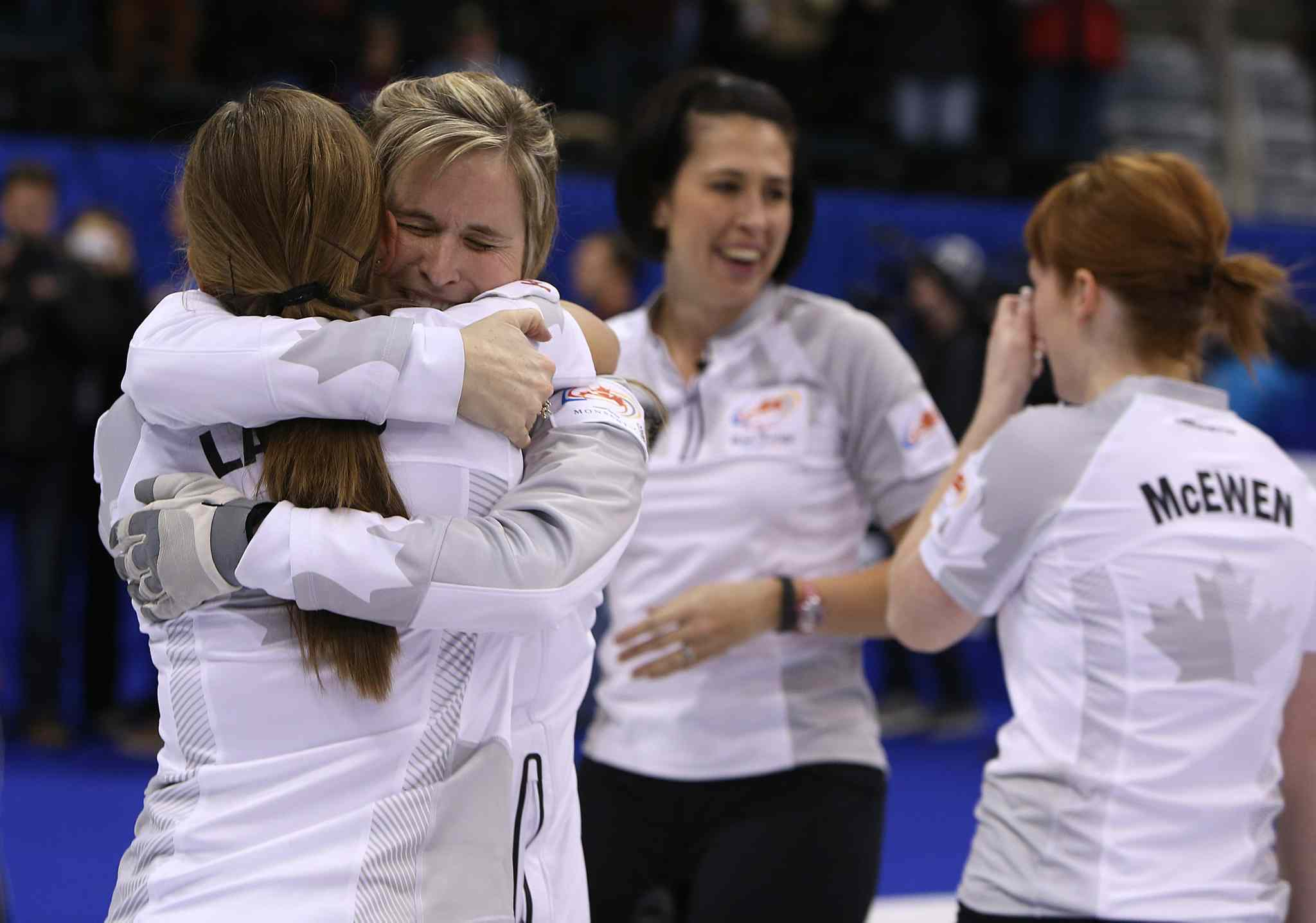 Skip Jennifer Jones (centre left) and Kaitlyn Lawes (left) hug as Jill Officer (centre right) and Dawn McEwen join the celebration.