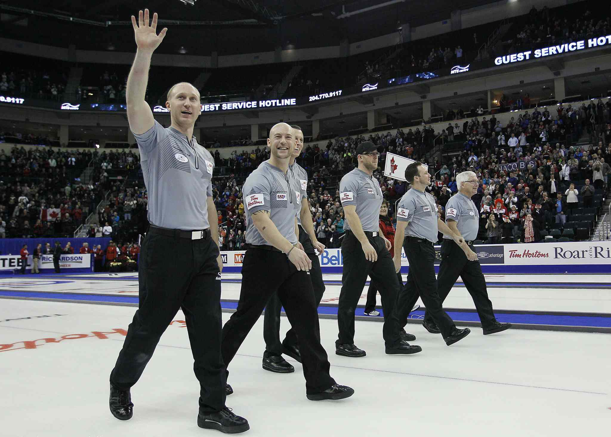 Skip Brad Jacobs (left) and his team acknowledge the crowd as they make their way down the ice after winning the final.