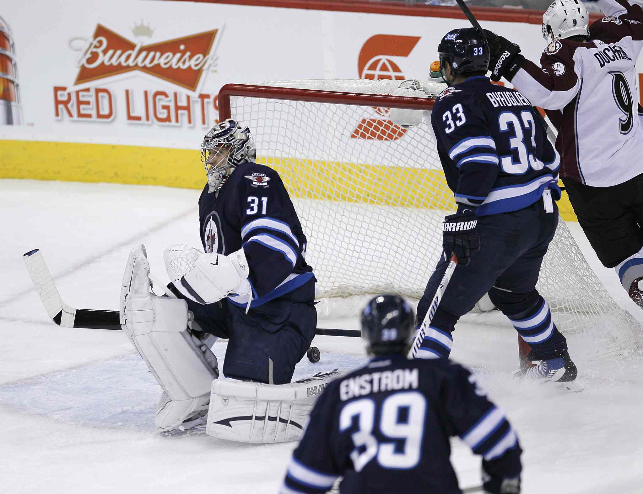 Colorado Avalanche's Matt Duchene (right) scores on Winnipeg Jets goaltender Ondrej Pavelec (left) as Jets defencemen Dustin Byfuglien (centre right) and Tobias Enstrom (right) looks on at the end of the first period.