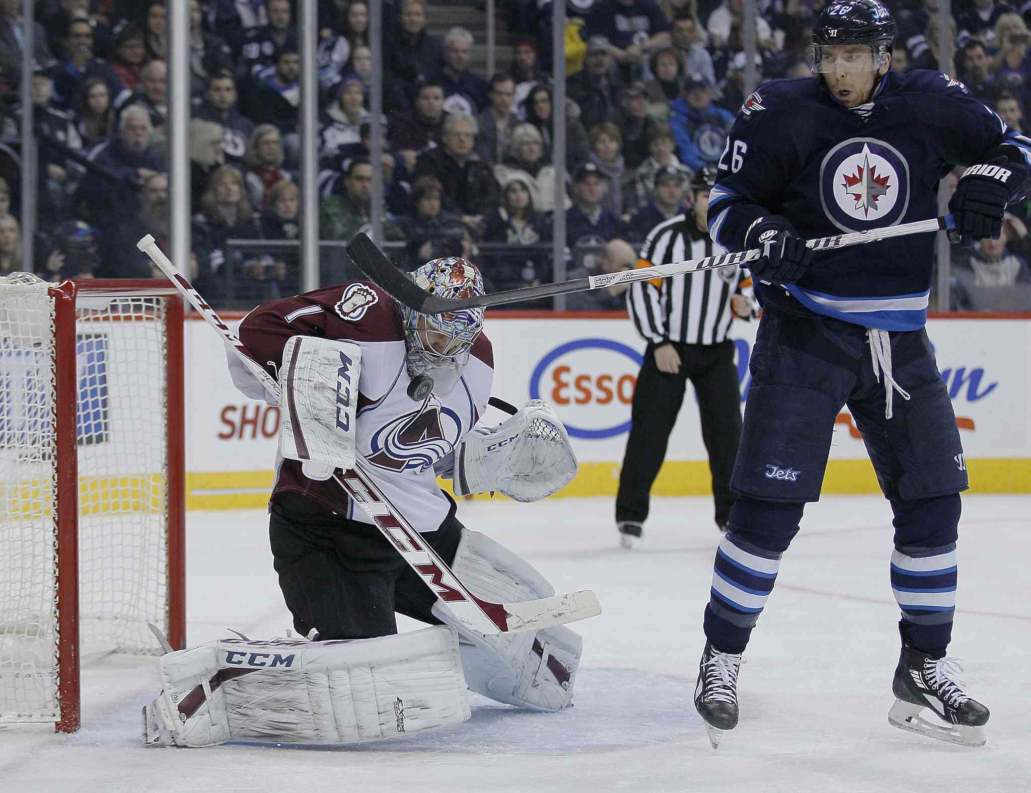 Blake Wheeler (right) tries a similar deflection in front of Varlamov during the second period.