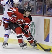 New Jersey Devils' Andy Greene (6) keeps the puck away from New York Rangers' Mats Zuccarello, of Norway, during the first period of an NHL hockey game game Saturday, March 22, 2014, in Newark, N.J. The Devils signed Greene to a long-term contract extension Wednesday. THE CANADIAN PRESS/ AP/Mel Evans