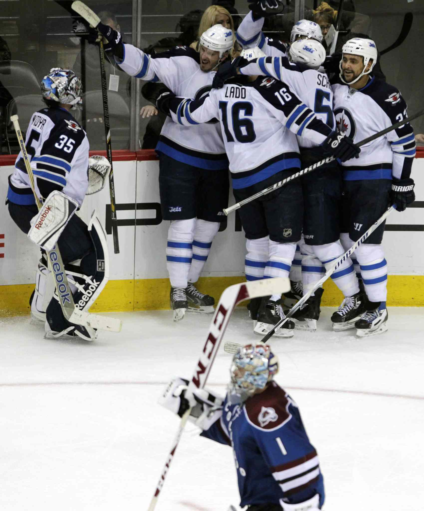 Winnipeg Jets goalie Al Montoya (left) skates toward his teammates to celebrate the team's overtime victory as Avalanche goalie Semyon Varlamov (bottom) skates to the bench.