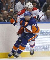 New York Islanders defenseman Calvin de Haan (44) checks Washington Capitals center Michael Latta (46) against the boards in the third period of Game 4 of a first-round NHL Stanley Cup hockey playoff series at Nassau Coliseum in Uniondale, N.Y., Tuesday, April 21, 2015. (AP Photo/Kathy Willens)
