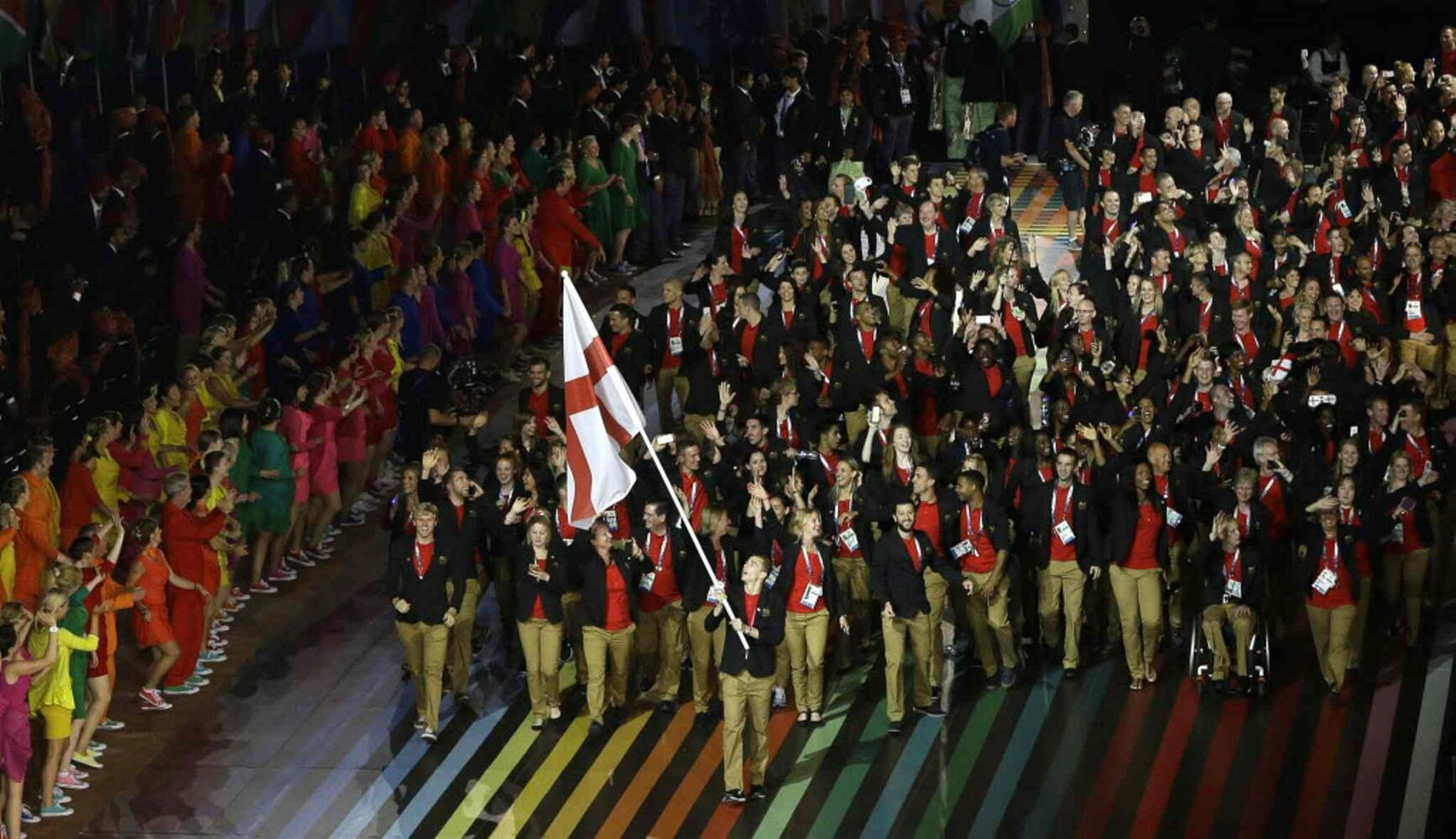 England's flag bearer Nick Matthews leads the team into the arena during the opening ceremony for the Commonwealth Games 2014. (Kirsty Wigglesworth / The Associated Press)