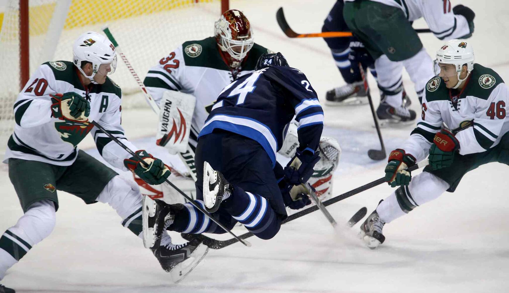 Minnesota Wild defenceman Ryan Suter (left) and Jared Spurgeon (right) trip up Winnipeg Jets defenceman Grant Clitsome during overtime. (TREVOR HAGAN / WINNIPEG FREE PRESS)