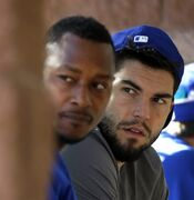 Kansas City Royals' Jarrod Dyson, left, and Eric Hosmer wait their turn in the batting cage during spring training baseball practice Wednesday, Feb. 25, 2015, in Surprise, Ariz. (AP Photo/Charlie Riedel)