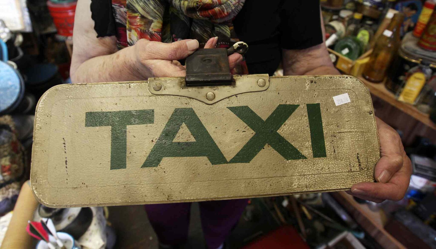 Vivian Proden holds old taxi sign for sale. Proden owns Junk for Joy just East of  Portage La Prairie, Manitoba on Hyw. #1 - Vivian, 84, is retiring after 34 years in the junk business and is having a 50% off sale starting this Friday.  ((JOE BRYKSA / WINNIPEG FREE PRESS))