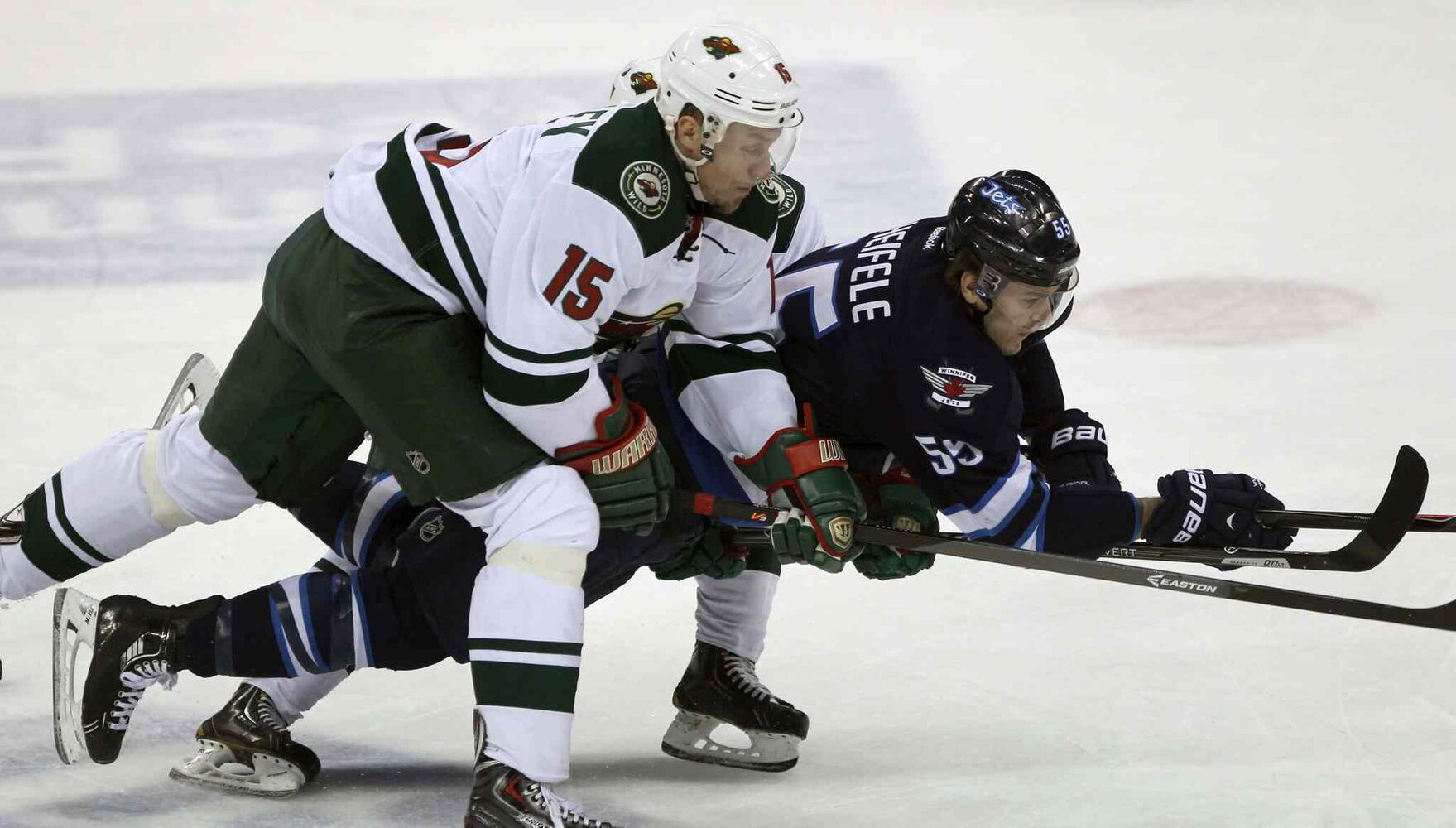 Winnipeg Jets forward Mark Scheifele (centre) gets hauled down by  Minnesota Wild skaters Dany Heatley (left) and Mikael Granlund during the first period. (JOE BRYKSA / WINNIPEG FREE PRESS)