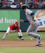 Texas Rangers second baseman Donnie Murphy, left, fields a hit as Seattle Mariners' Corey Hart, right, runs to second during the seventh inning of a baseball game on Thursday, April 17, 2014, in Arlington, Texas. Texas won 8-6. (AP Photo/Brandon Wade)