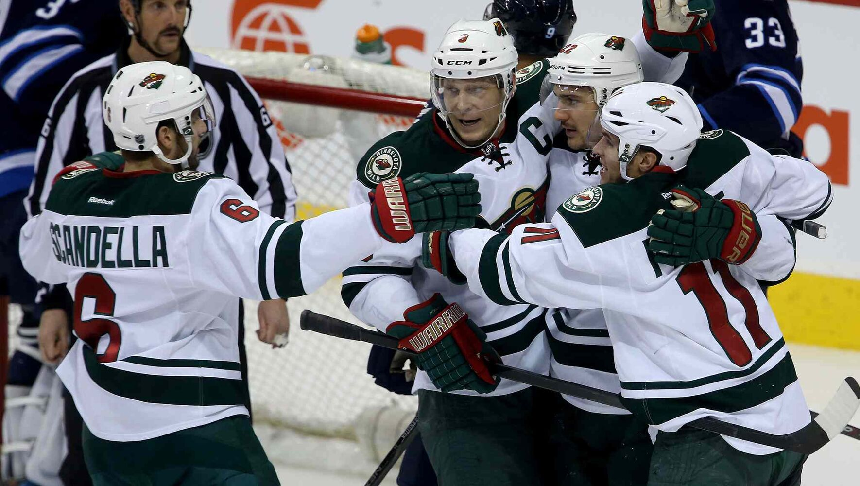 Minnesota Wild skaters Marco Scandella (left), Mikko Koivu (centre left), Nino Niederreiter (centre right) and Zach Parise celebrate after Niederreiter scored during the third period. (TREVOR HAGAN / WINNIPEG FREE PRESS)