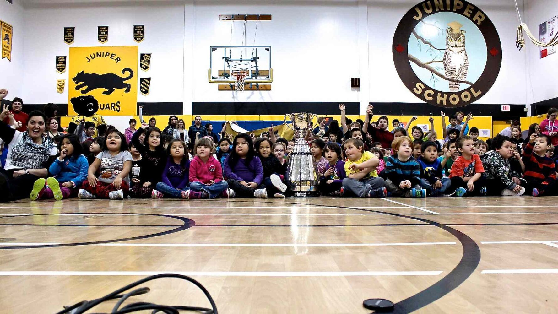 Juniper Elementary School, home of the Jaguars, pose for a group photo with the Grey Cup. The trophy was in town as part of an eight-day tour through northern Manitoba to help promote the Grey Cup game in Winnipeg this year.
