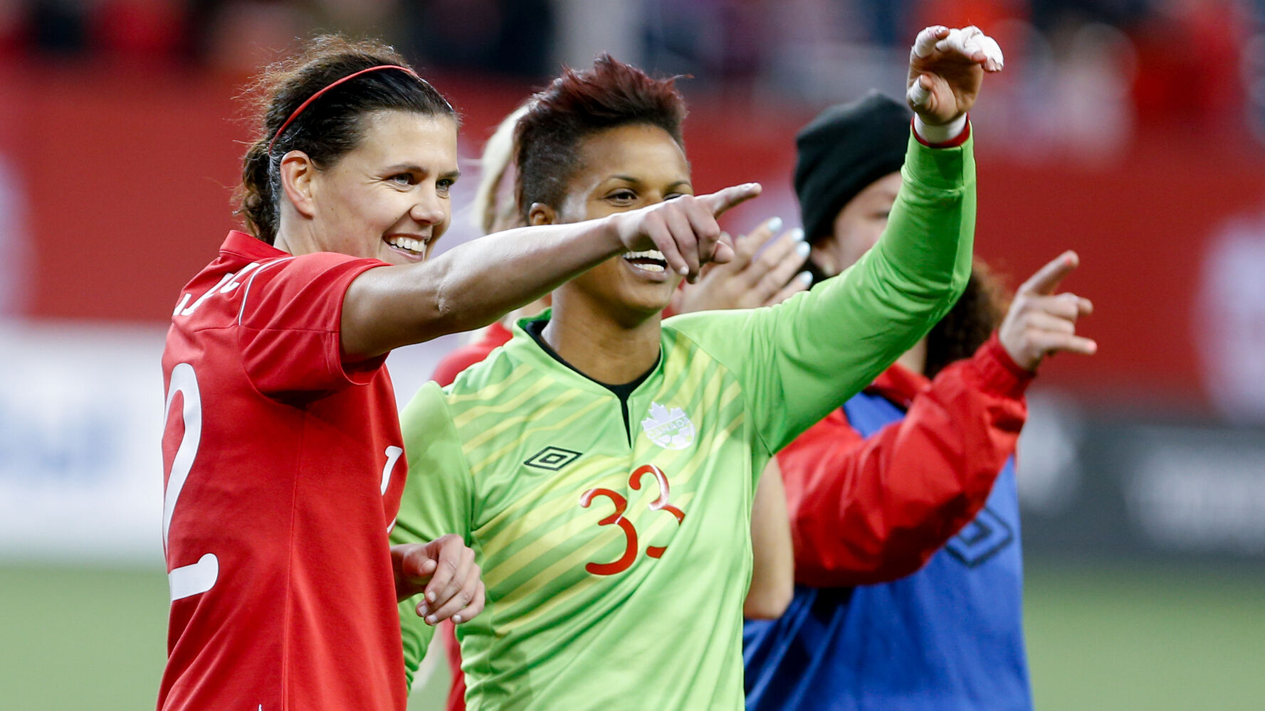 Canada forward Christine Sinclair point to fans in crowd with goalkeeper Karina LeBlanc at the end of their match against USA at Investors Group Field. (Melissa Tait / Winnipeg Free Press)