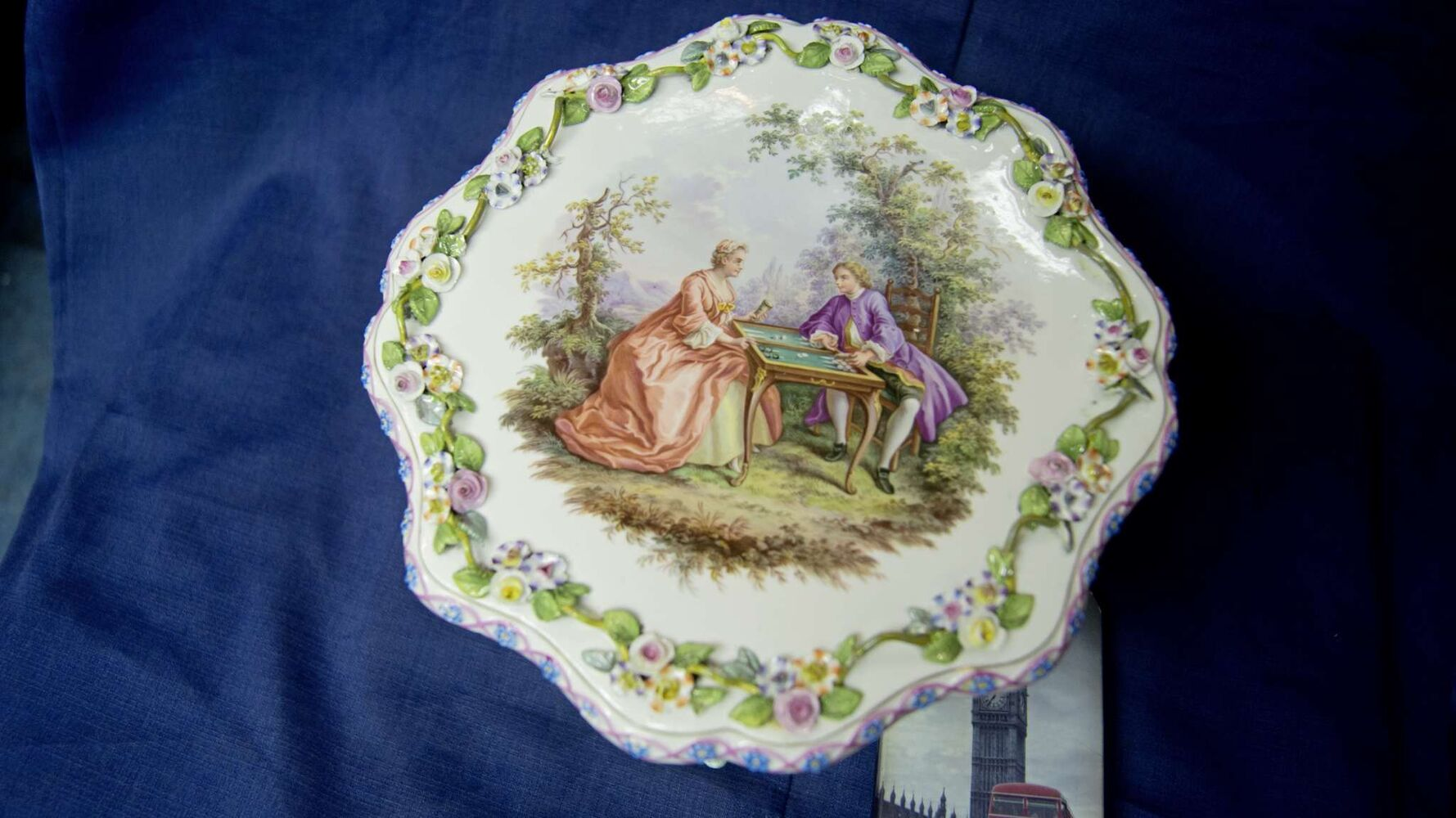 """What is one piece you would be sad to see go? This hand painted decorative table, about three times as large as a smart phone, is a masterpiece by Cooper's standards. It was crafted by Meissen porcelain in Germany, circa 1850.  """"That's the finest, best hand painting I've ever seen on anything. It is amazing."""" (Danielle Da Silva - Sou'wester)"""