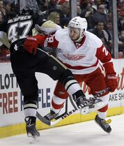 Pittsburgh Penguins' Simon Despres (47) is pushed against the boards by Detroit Red Wings' Landon Ferraro (29) during the second period of an NHL hockey game Thursday, March 20, 2014, in Detroit. The Red Wings have signed Ferraro to a one-year contract. THE CANADIAN PRESS/AP Photo/Duane Burleson)