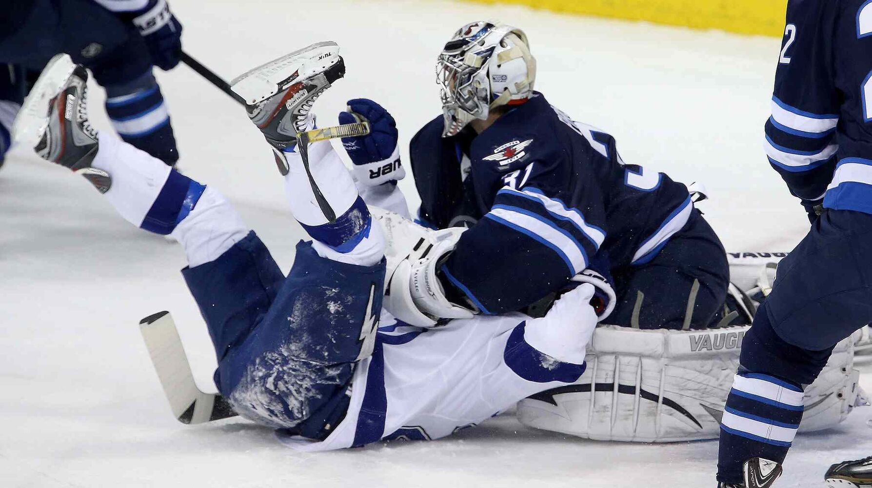 Tampa Bay Lightning's Martin St. Louis (26) is smothered by Winnipeg Jets' goaltender Ondrej Pavelec (31) during the first period.