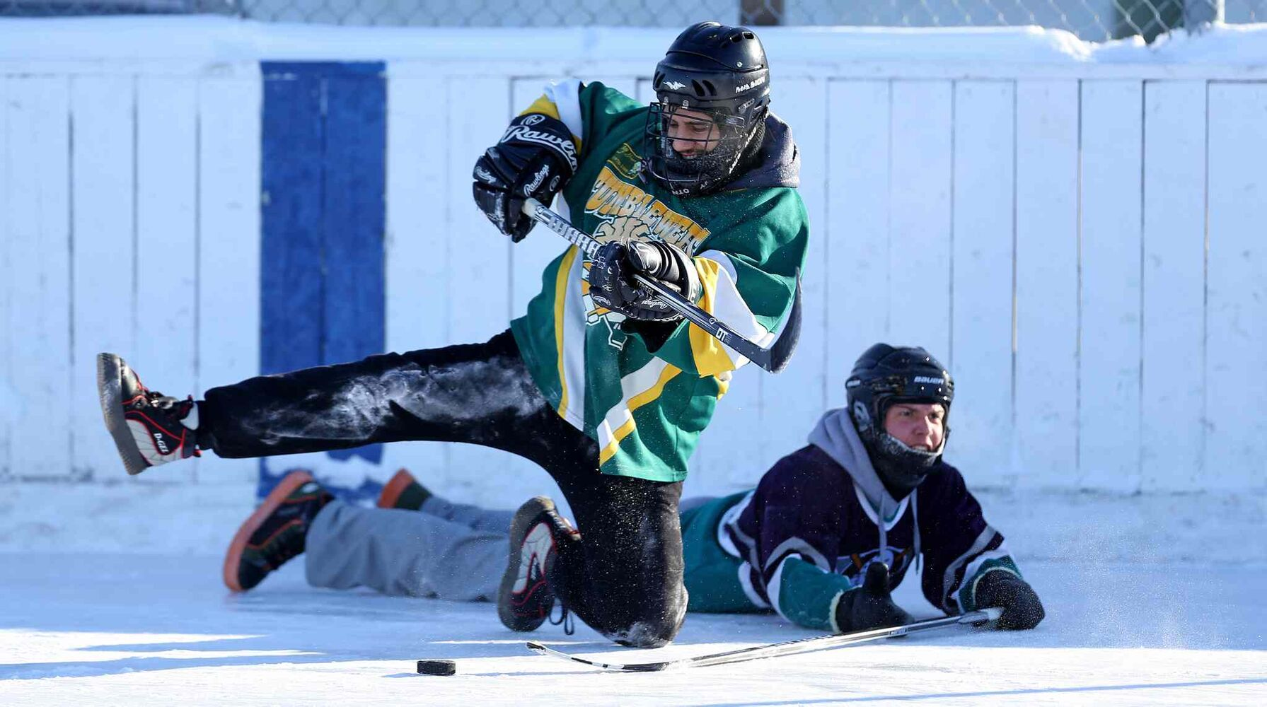 Kyle Macpherson of the Tumbleweeds plays the puck from his knee after getting tangled up with one of the Mighty Puckin' Drunks during a spongee game. (Trevor Hagan / Winnipeg Free Press)
