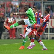 Bayern's David Alaba from Austria, right, Bayern's Juan Bernat from Spain, center, and Wolfsburg's Josuha Guilavogui from France challenge for the ball during the soccer match between FC Bayern Munich and VfL Wolfsburg in the Allianz Arena in Munich, Germany, on Friday, Aug. 22. 2014. (AP Photo/Kerstin Joensson)