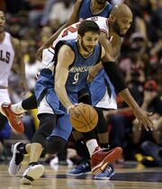 Minnesota Timberwolves' Ricky Rubio, front, and Chicago Bulls' Taj Gibson reach for a loose ball during the first half of a preseason NBA basketball game Friday, Oct. 24, 2014, in St. Louis. (AP Photo/Jeff Roberson)