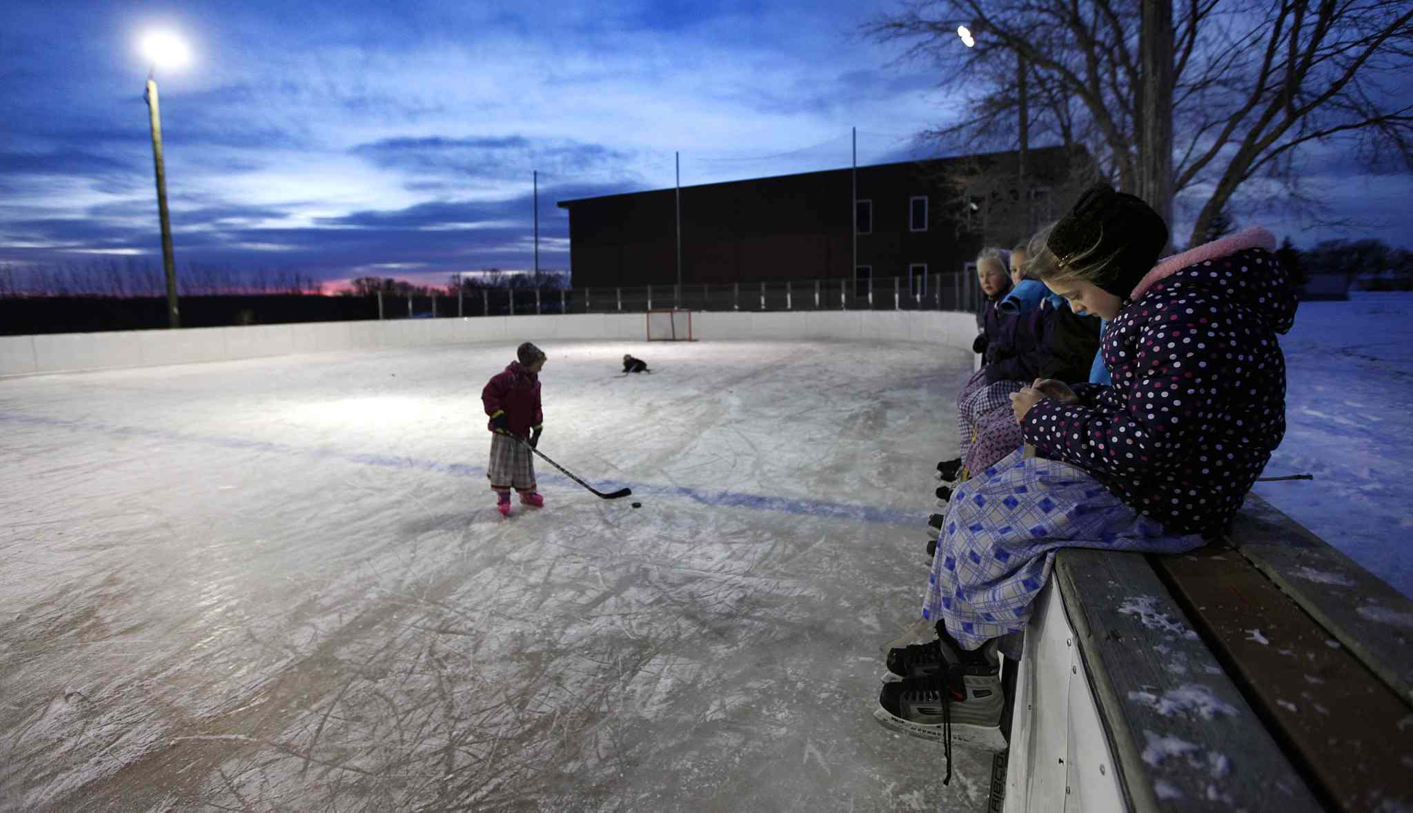 Women and children at the Baker Community gather on the ice after school.  (Phil Hossack / Winnipeg Free Press)