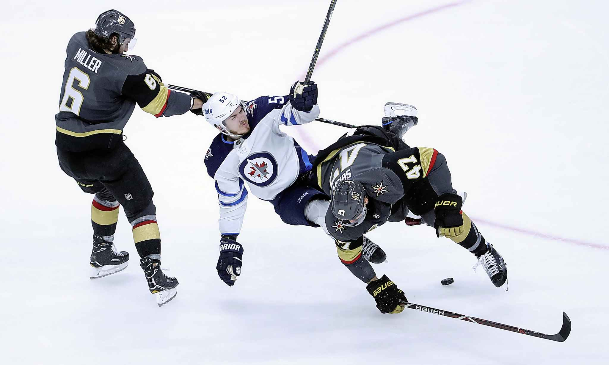 Vegas Golden Knights' Luca Sbisa (47) hits Winnipeg Jets' Jack Roslovic (52) in front of Colin Miller (6) during the second period of game 4 of their Western Conference Final series in Las Vegas, Friday, May 18, 2018.
