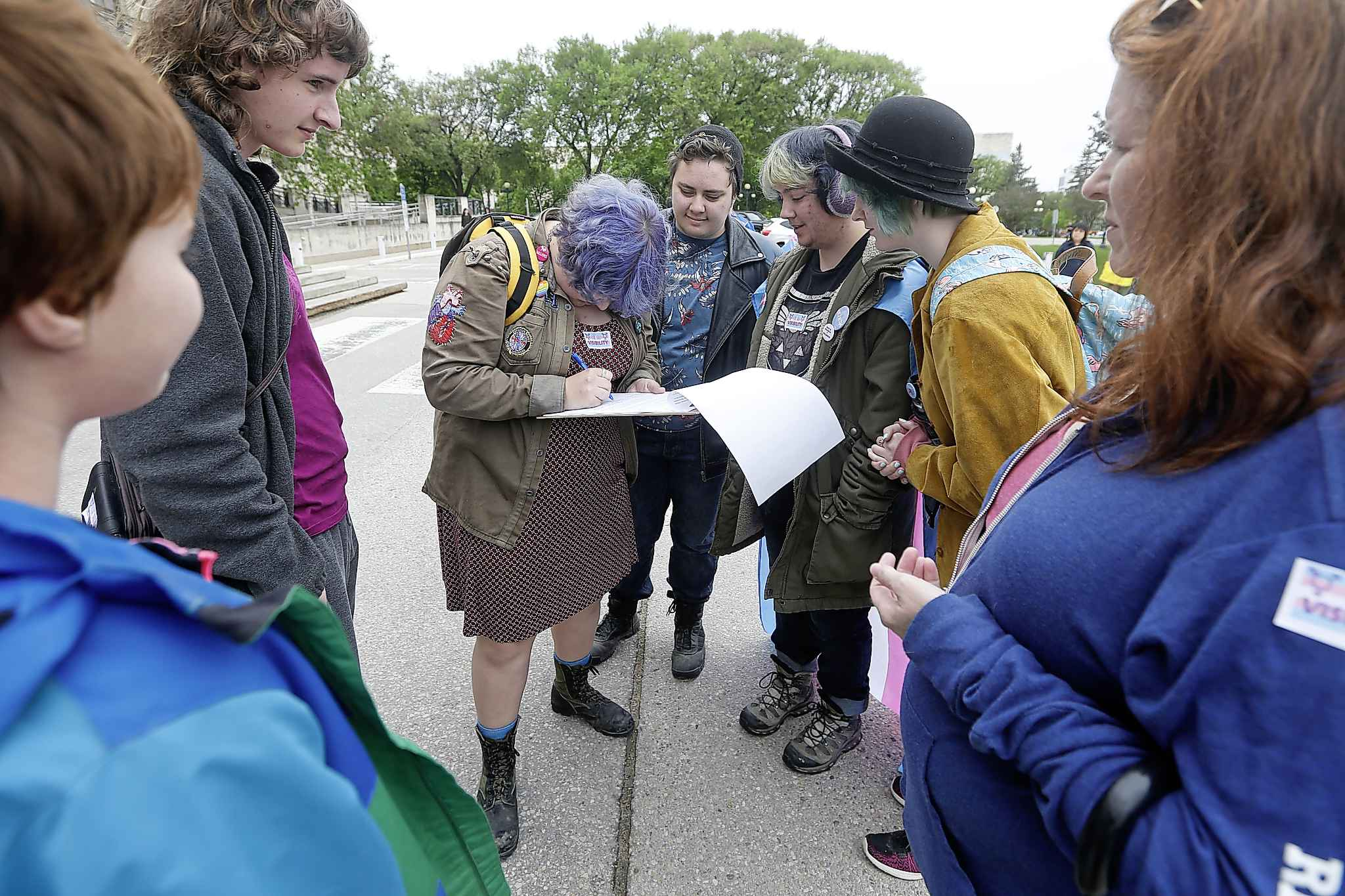 People sign petitions for gender-neutral identification at a transgender rally and march at the Manitoba legislature last summer. (John Woods / Winnipeg Free Press files)