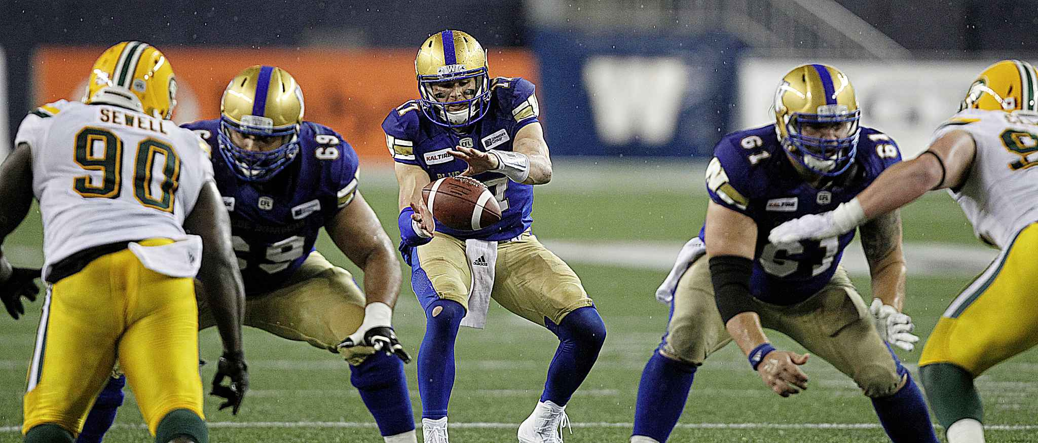 PHIL HOSSACK / WINNIPEG FREE PRESS - Winnipeg Blue Bomber QB #17 Chris Streveler takes the snap in the 2nd quarter when play resumed after a weather delay Thursday at Investor's Group Field. Play was called due to weather again before the quarter ended.  - June 14, 2018