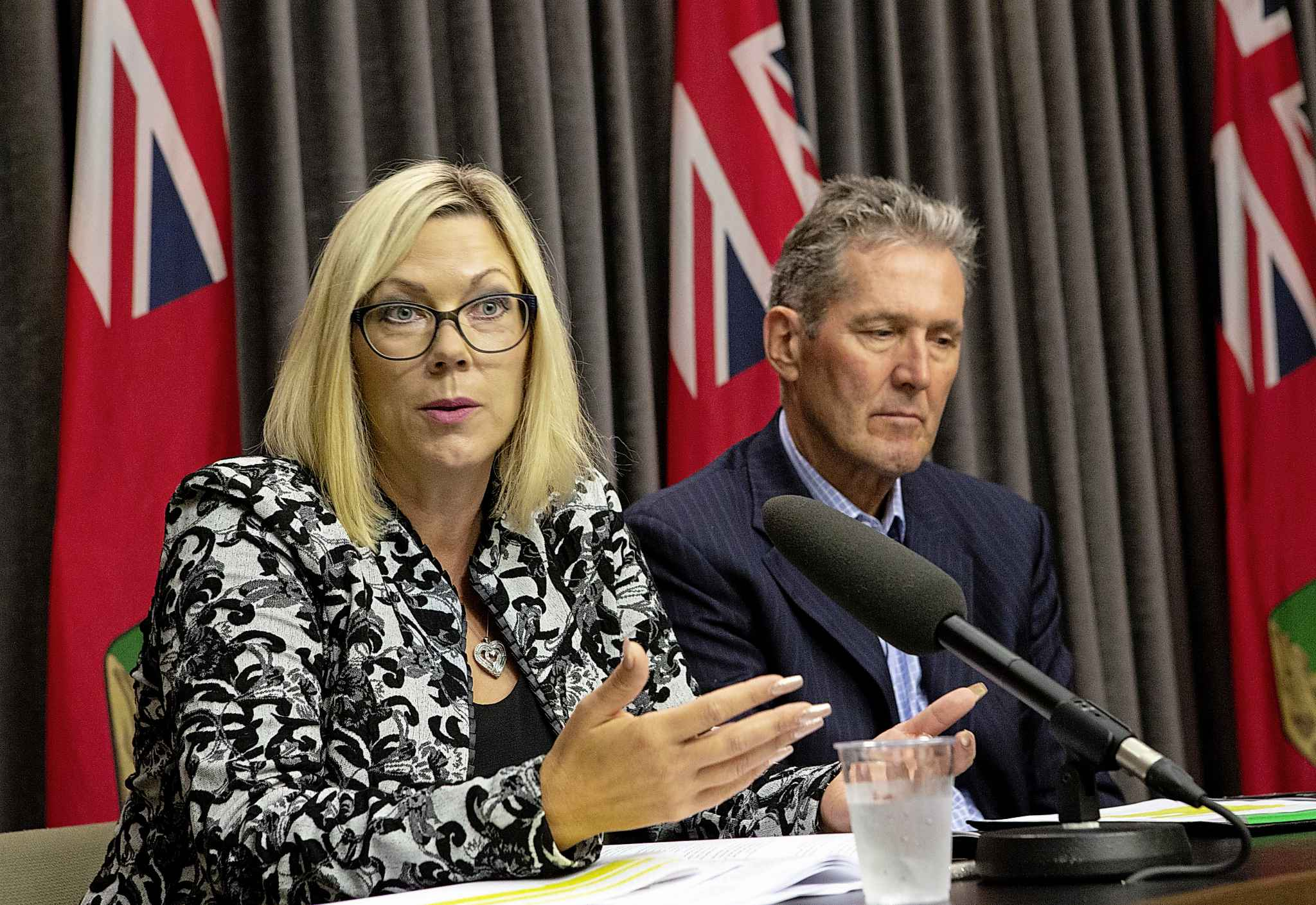 Manitoba Premier Brian Pallister, right, listens as Sustainable Development Minister Rochelle Squires discusses a recent report detailing workplace sexual harassment and measures taken to mitigate it in government at the Manitoba Legislature building press room.