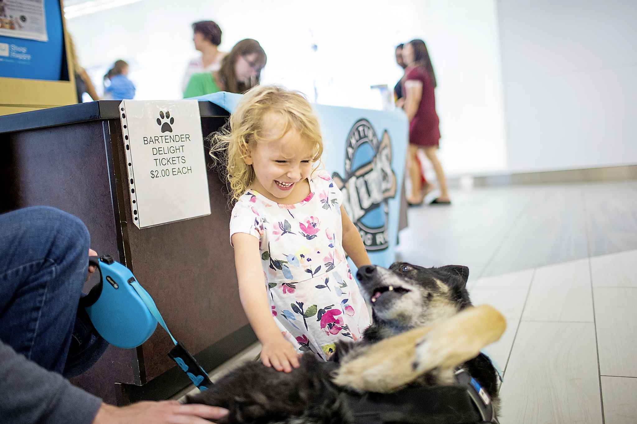 Four-year-old Clara Loney gives Barbie a belly rub at the Manitoba Mutts booth at Kildonan Place on Saturday. (Mikaela MacKenzie / Winnipeg Free Press)