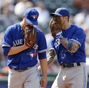 Toronto Blue Jays infielder Brett Lawrie, right, talks with Toronto Blue Jays relief pitcher Aaron Loup after Loup gave up a three RBI-double in the sixth inning of a baseball game, Sunday, April 20, 2014, in Cleveland. (AP Photo/Tony Dejak)