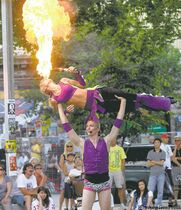 Terrebelle Murphy is hoisted into the air by partner Rusty Hammond in Old Market Square during the Winnipeg Fringe Festival.