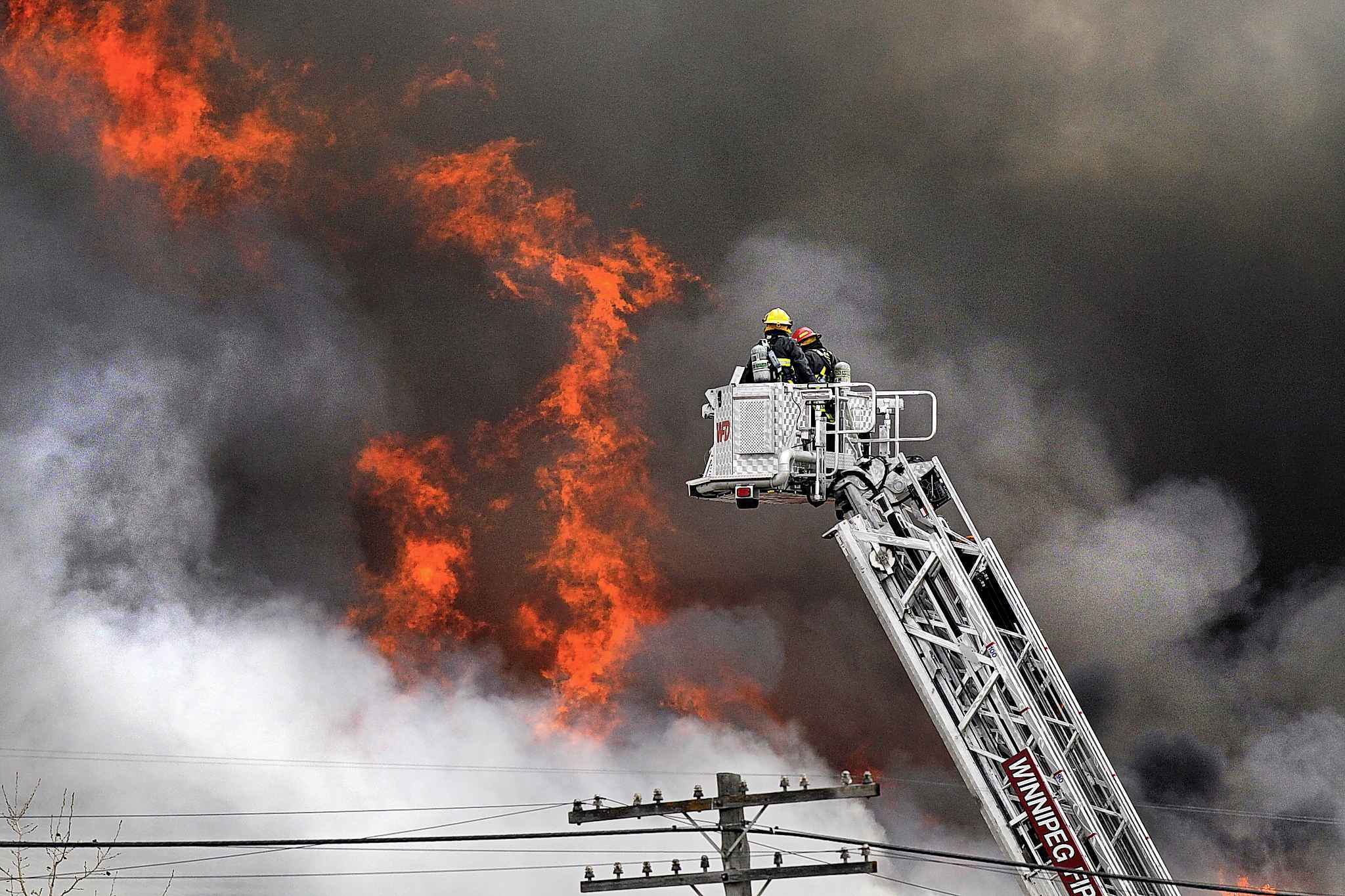 Firefighters position an aerial ladder truck while fighting a fire at an oilseed plant in St. Boniface.