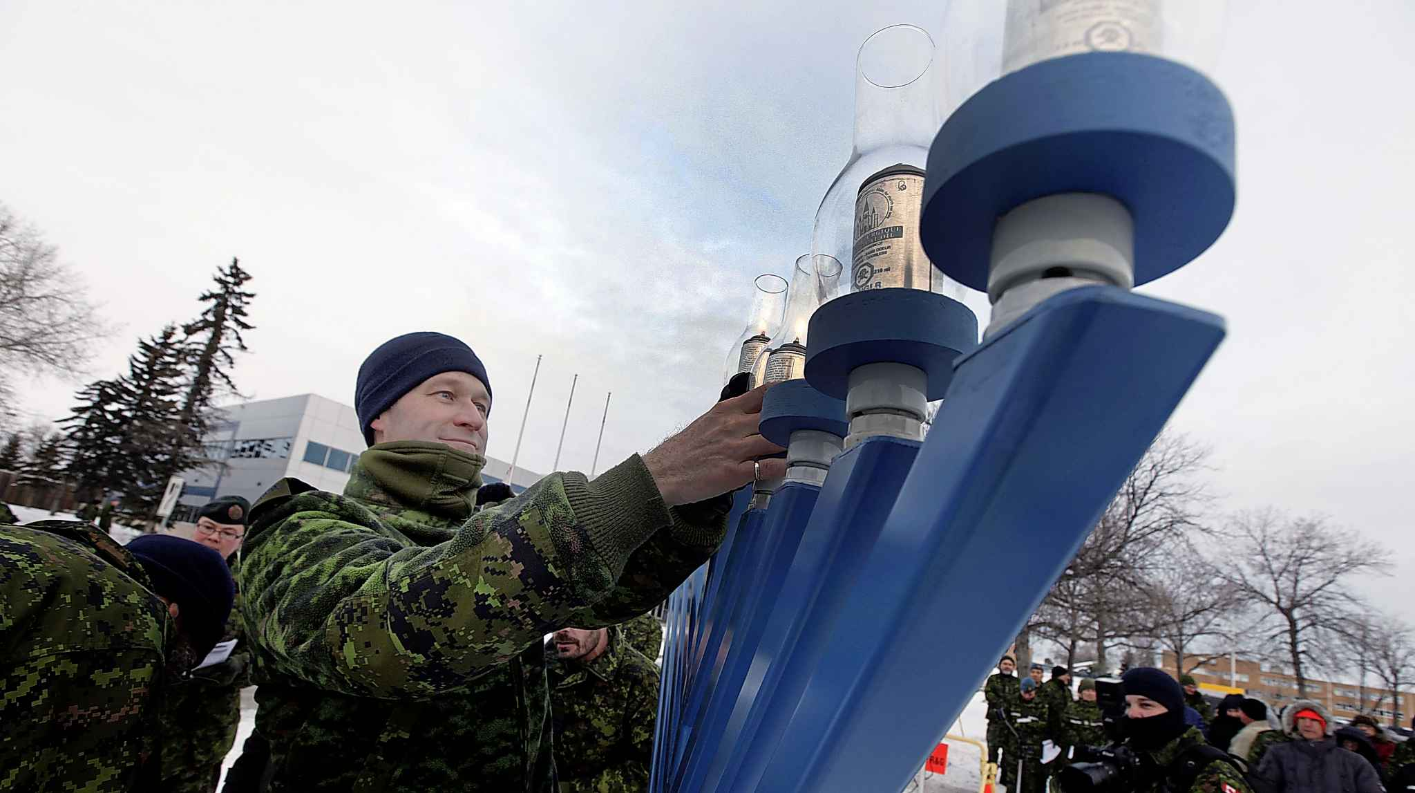 Col. Charron places lit candles on the menorah at 17 Wing in December 2018. (Phil Hossack / Winnipeg Free Press files)