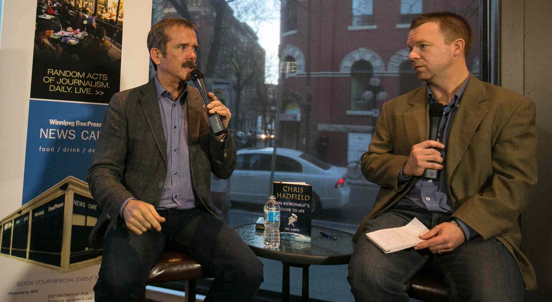 Col. Chris Hadfield (left) talks with reporter Geoff Kirybson on the intricacies of space flight to a packed Winnipeg Free Press News Café on Wednesday. (Melissa Tait / Winnipeg Free Press)