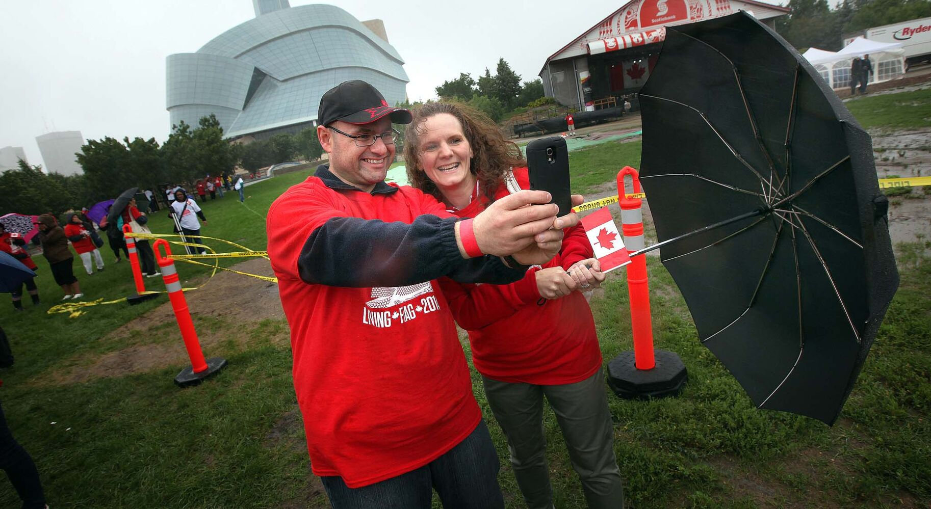 Ward Bruner and Jennifer Wilson hang onto their umbrella and smart phone trying to take a selfie in the blowing rain before taking part in the flag event. (Phil Hossack / Winnipeg Free Press)