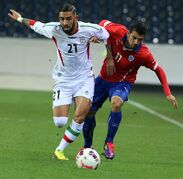 Iran's Ashkan Dejagah, left, challenges Chile's Mark Gonzalez for the ball during the friendly soccer match between Iran and Chile in St. Poelten, Austria, Thursday, March 26, 2015. (AP Photo/Ronald Zak)