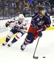 Columbus Blue Jackets' David Savard (58) keeps the puck away from Washington Capitals' Evgeny Kuznetsov (92), of Russia, in the first period of an NHL hockey game, Tuesday, Jan. 27, 2015, in Columbus, Ohio. (AP Photo/Mike Munden)