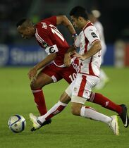 Equatorial Guinea's captain Emilio Nsue, left, evades tackle from Tunisia's Hamza Mathlouthi, right, during their African Cup of Nations quarter final soccer match in Bata, Equatorial Guinea, Saturday, Jan. 31, 2015. (AP Photo/Themba Hadebe)