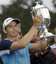 Camilo Villegas, of Colombia, holds the Sam Snead trophy on the 18th green after winning the Wyndham Championship golf tournament in Greensboro, N.C., Sunday, Aug. 17, 2014. (AP Photo/Gerry Broome)