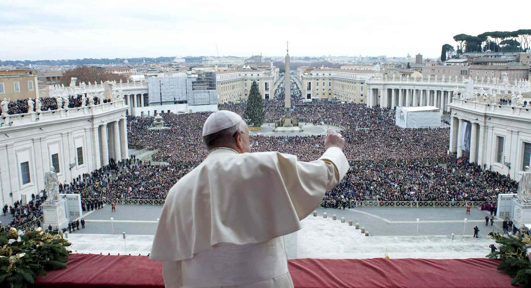 "In this picture provided by the Vatican newspaper L'Osservatore Romano, Pope Francis delivers his ""Urbi et Orbi"" (to the City and to the World) message from the central balcony of St. Peter's Basilica at the Vatican, Wednesday, Dec. 25, 2013. Pope Francis on Christmas day is wishing for a better world, with peace for the land of Jesus' birth, for Syria and Africa as well as for the dignity of migrants and refugees fleeing misery and conflict. Francis spoke from the central balcony of St. Peter's Basilica Wednesday to tens of thousands of tourists, pilgrims and Romans in the square below. He said he was joining in the song of Christmas angels with all those hoping ""for a better world,"" and with those who ""care for others, humbly.""  (L'Osservatore Romano)"