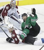 Dallas Stars right wing Erik Cole (72) is knocked off his feet by Colorado Avalanche defenseman Jan Hejda (8) as goalie Semyon Varlamov (1) looks on during the third period of an NHL hockey game Friday, Feb. 27, 2015, in Dallas. The Avalanche won 5-4. (AP Photo/LM Otero)