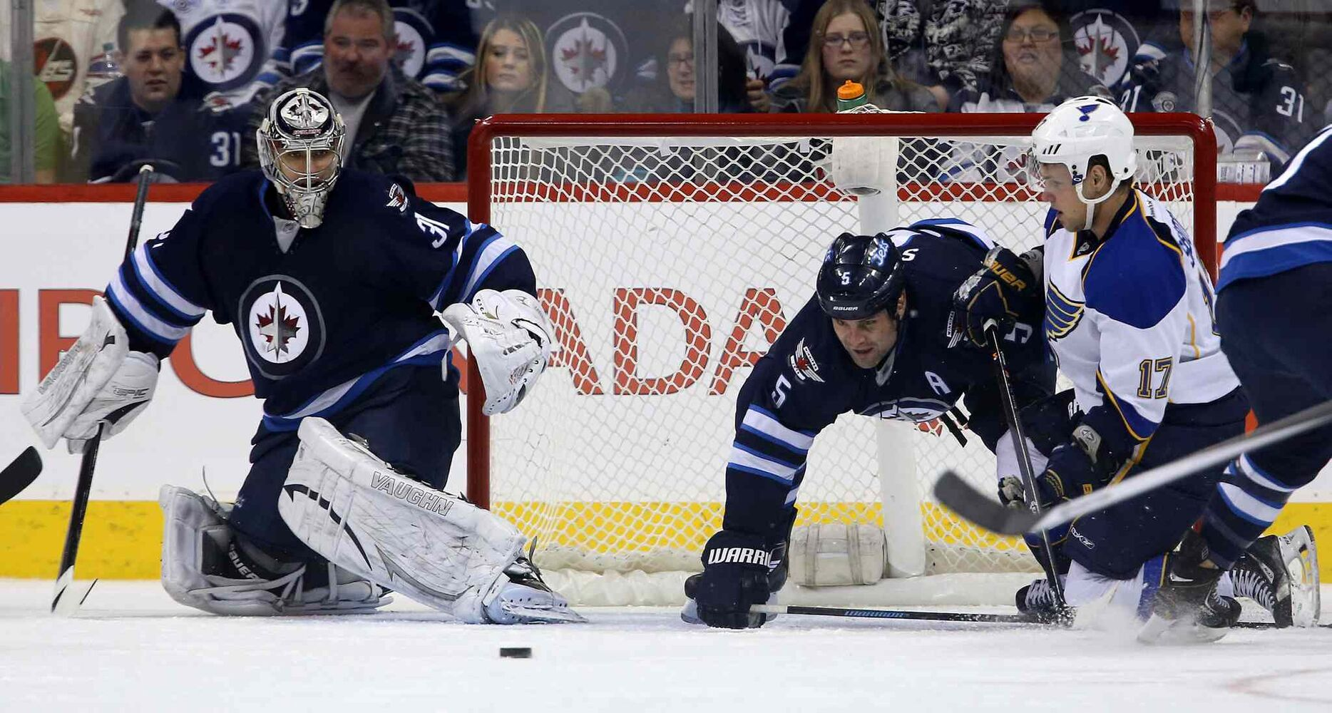 Winnipeg Jets goaltender Ondrej Pavelec watches as Jets defenceman Mark Stuart and St. Louis Blues' Vladimir Sobotka battle for the puck during the second period. (TREVOR HAGAN / THE CANADIAN PRESS)