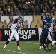 Winnipeg Blue Bombers Teague Sherman trys to block Montreal Alouettes QB Jonathan Crompton during first half CFL action at Investors Group Field in Winnipeg Friday night.