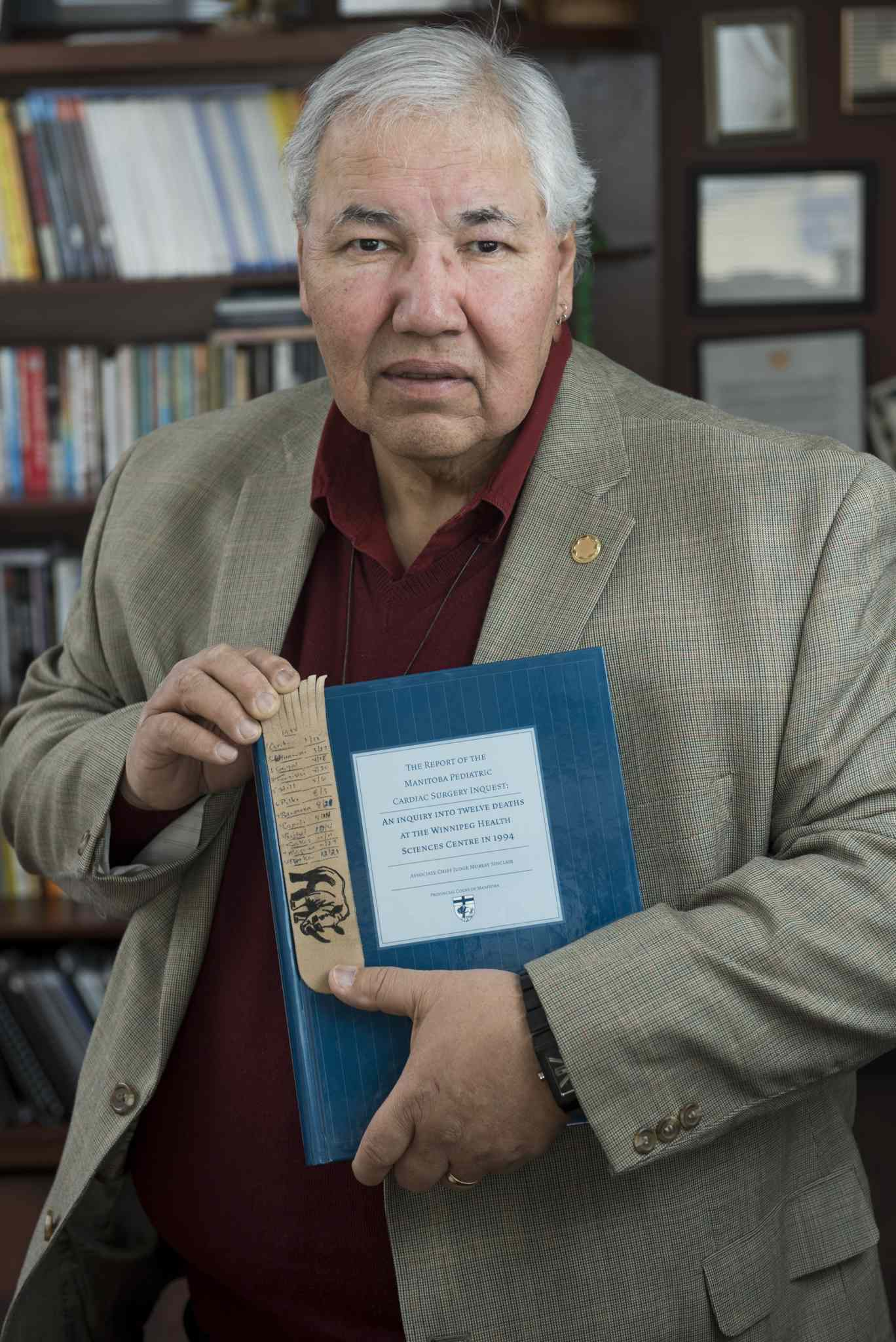 Murray Sinclair, the judge of the Pediatric Cardiac Inquest, with the inquest report and the bookmark.