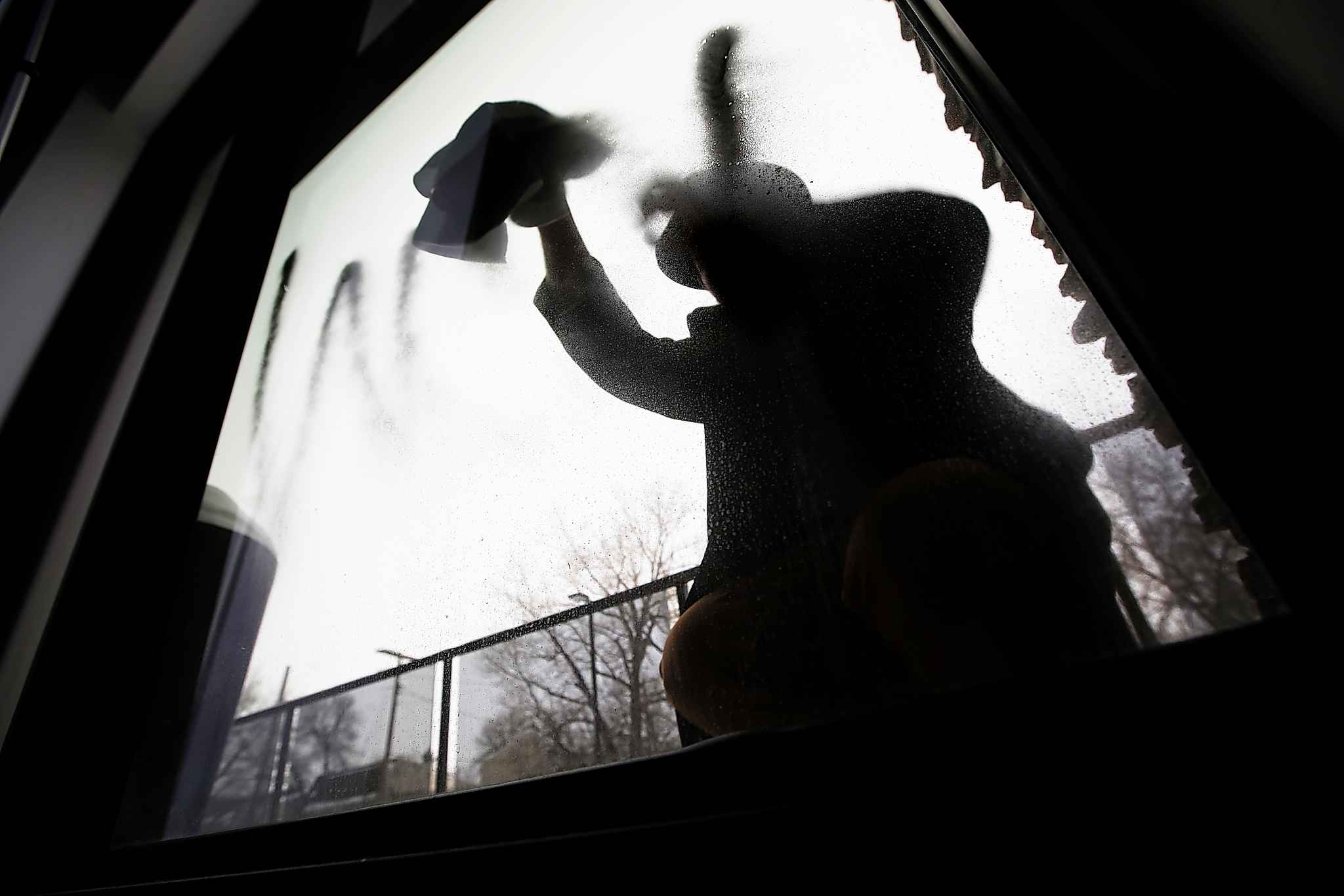 JOHN WOODS / WINNIPEG FREE PRESS</p><p>Maxim Berent, an owner of a Corydon Avenue cafe and who does not want to be identified in photograph, tries to clean anti-Semitic graffiti off his business window in Winnipeg Sunday, Feb. 3, 2019.</p>