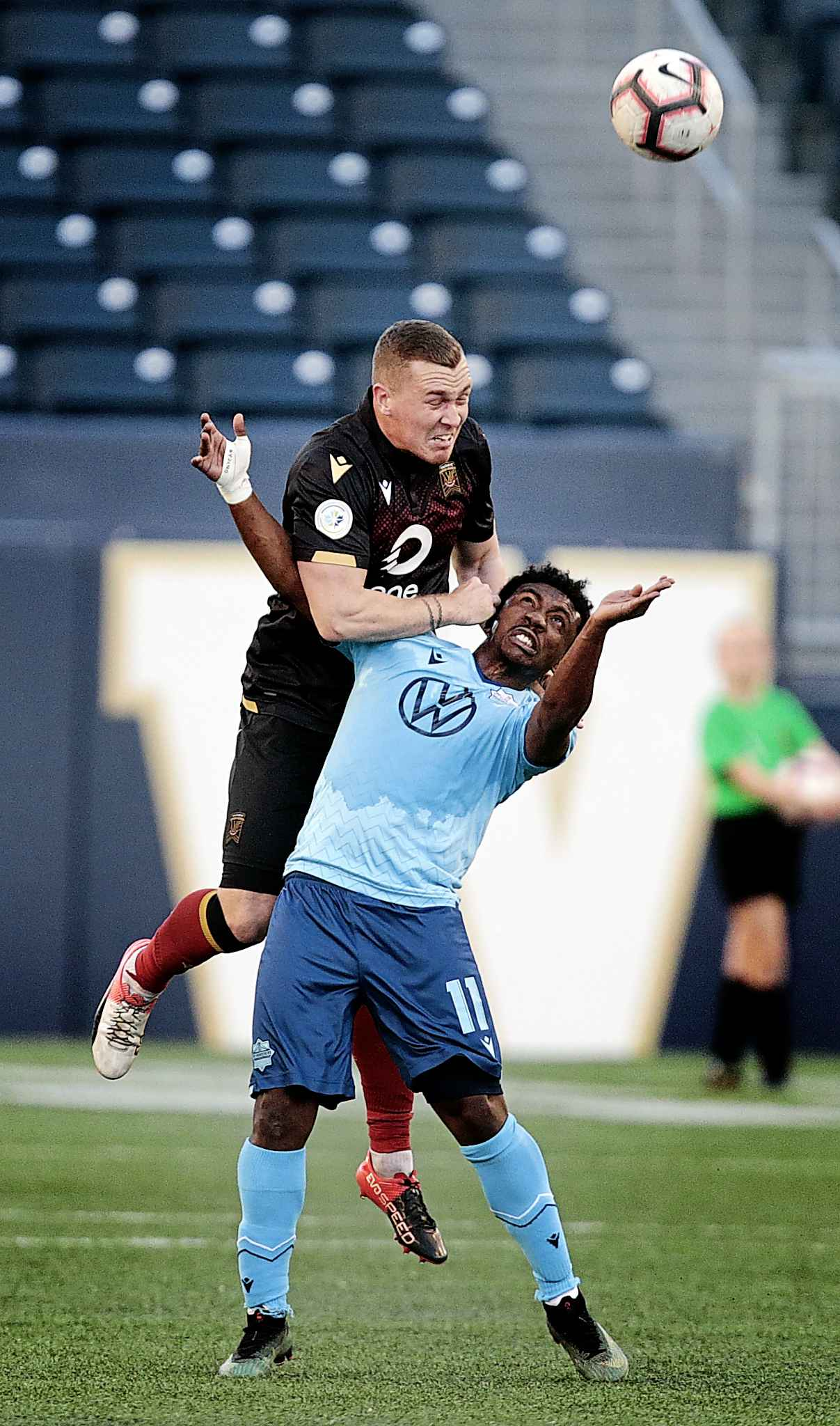 Valour FC's Adam Mitter heads the ball while holding HFX Wanderer's Akeem Garcia down on the ground at IG Field, Wednesday. PHIL HOSSACK / WINNIPEG FREE PRESS