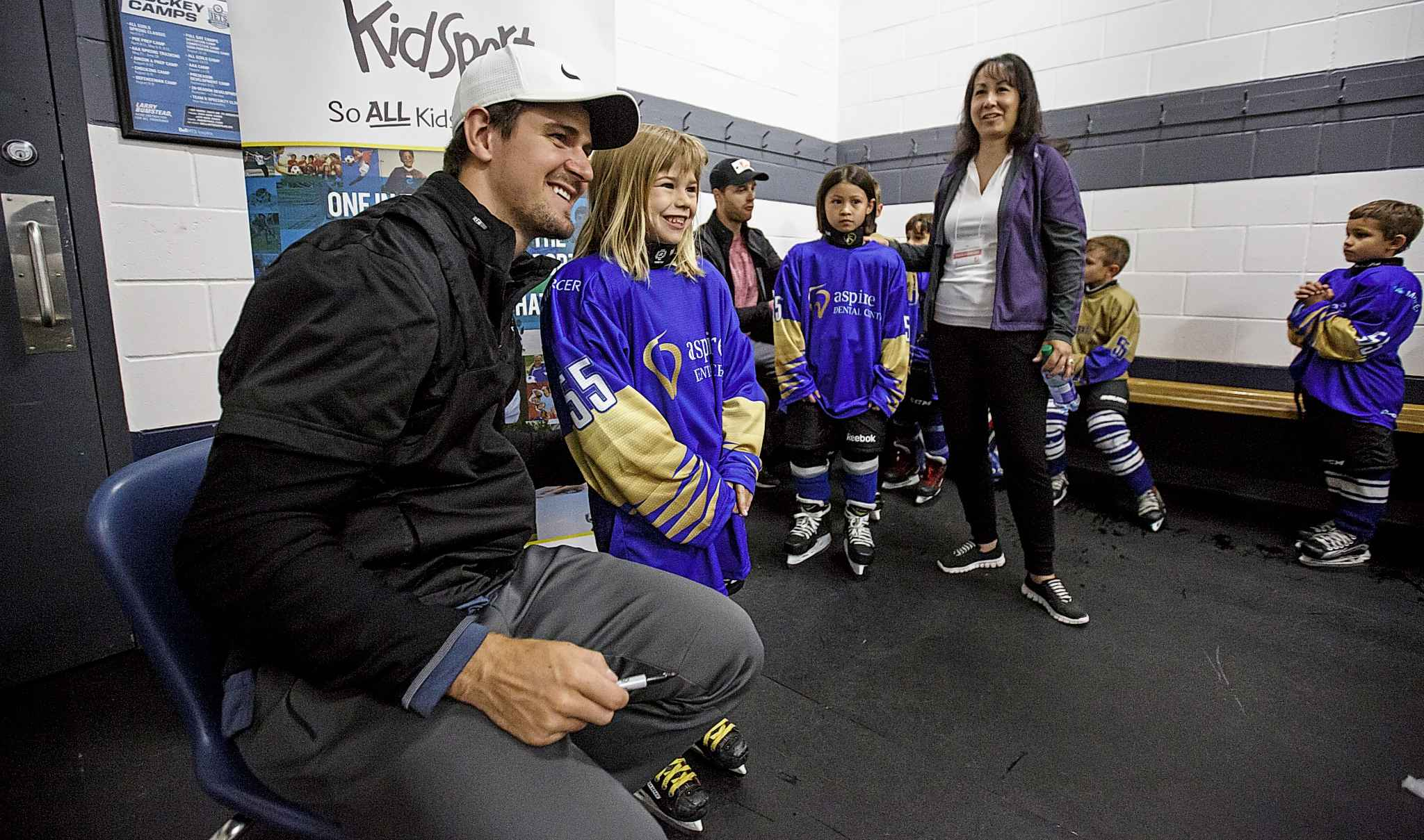 Mark Scheifele signs Lily Benjaminson's jersey and poses for a photo Saturday. (Mike Deal / Winnipeg Free Press)