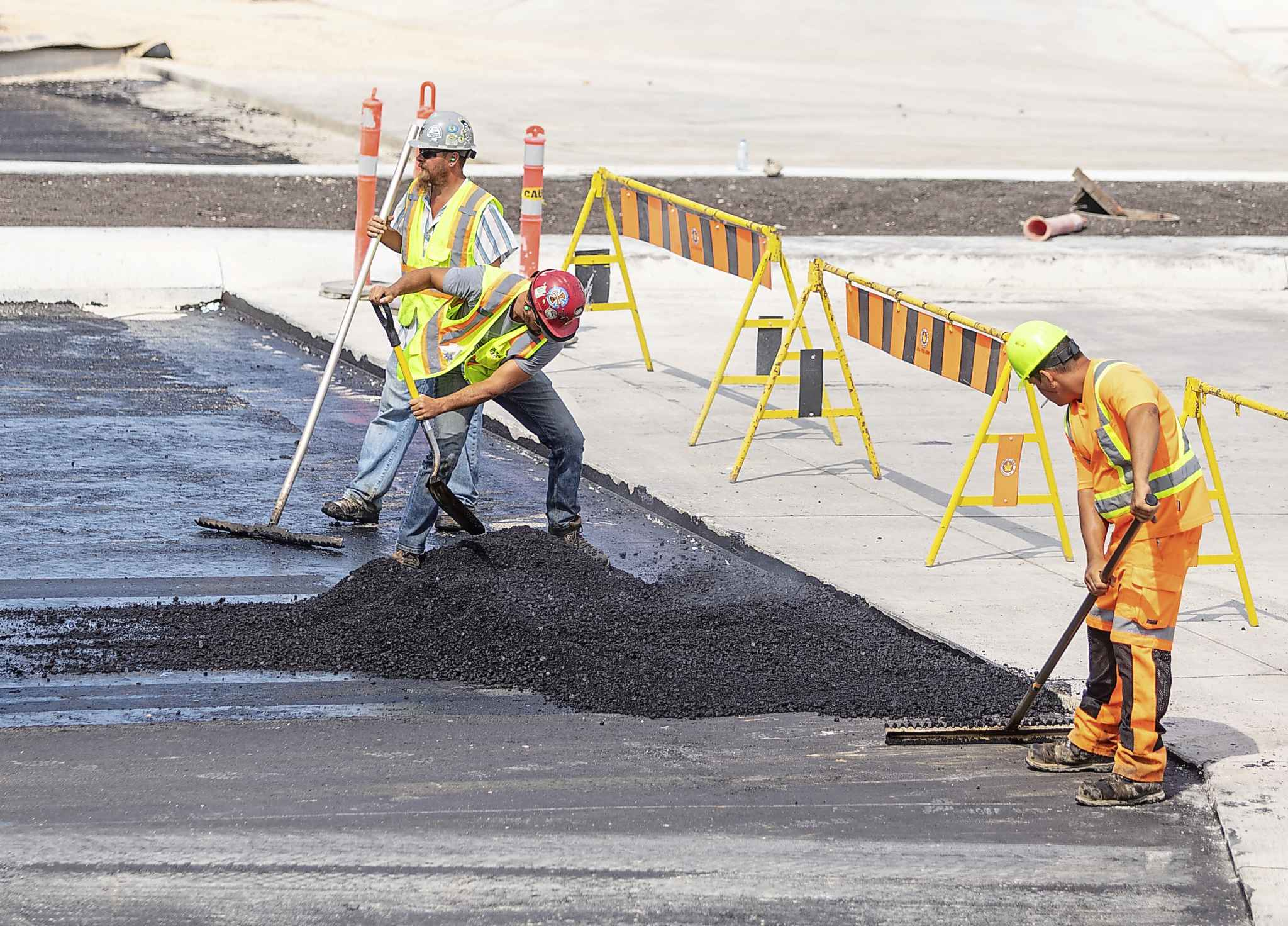 Construction crews put down layer of asphalt on the roadway through the Waverly underpass on Wednesday afternoon.