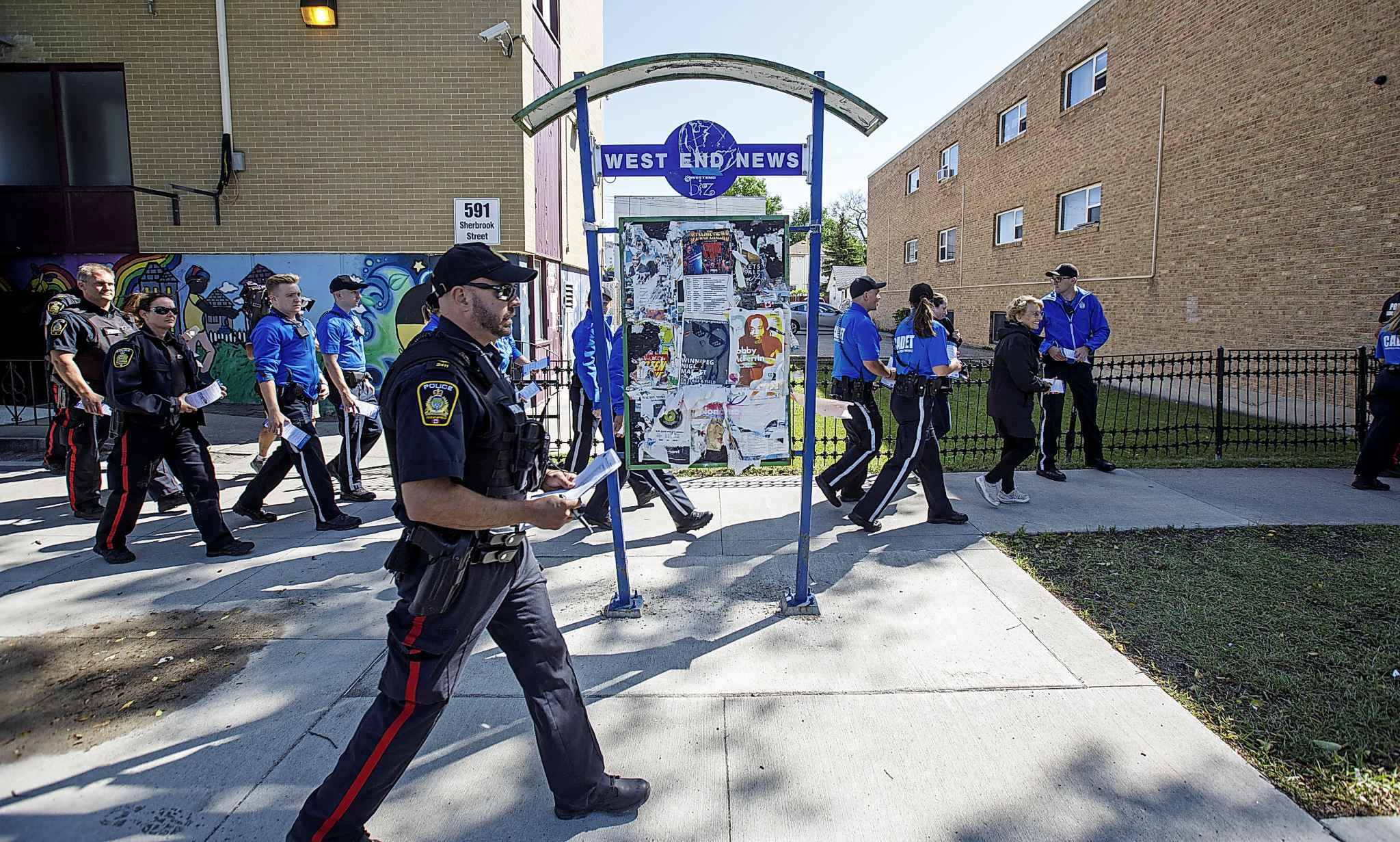 Winnipeg Police Service officers and cadets going door-to-door talking to residents along Sherbrook Street about how community members can help in crime prevention and reminding people of the various ways they can connect with the WPS. (MIke Deal / Winnipeg Free Press files)